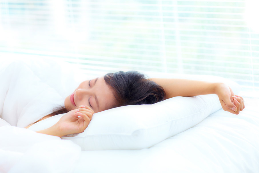 Light-airy-bedroom-young-woman-happily-resting-in-bed