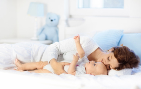 Mom-cuddling-with-baby-on-white-sheets-in-bed