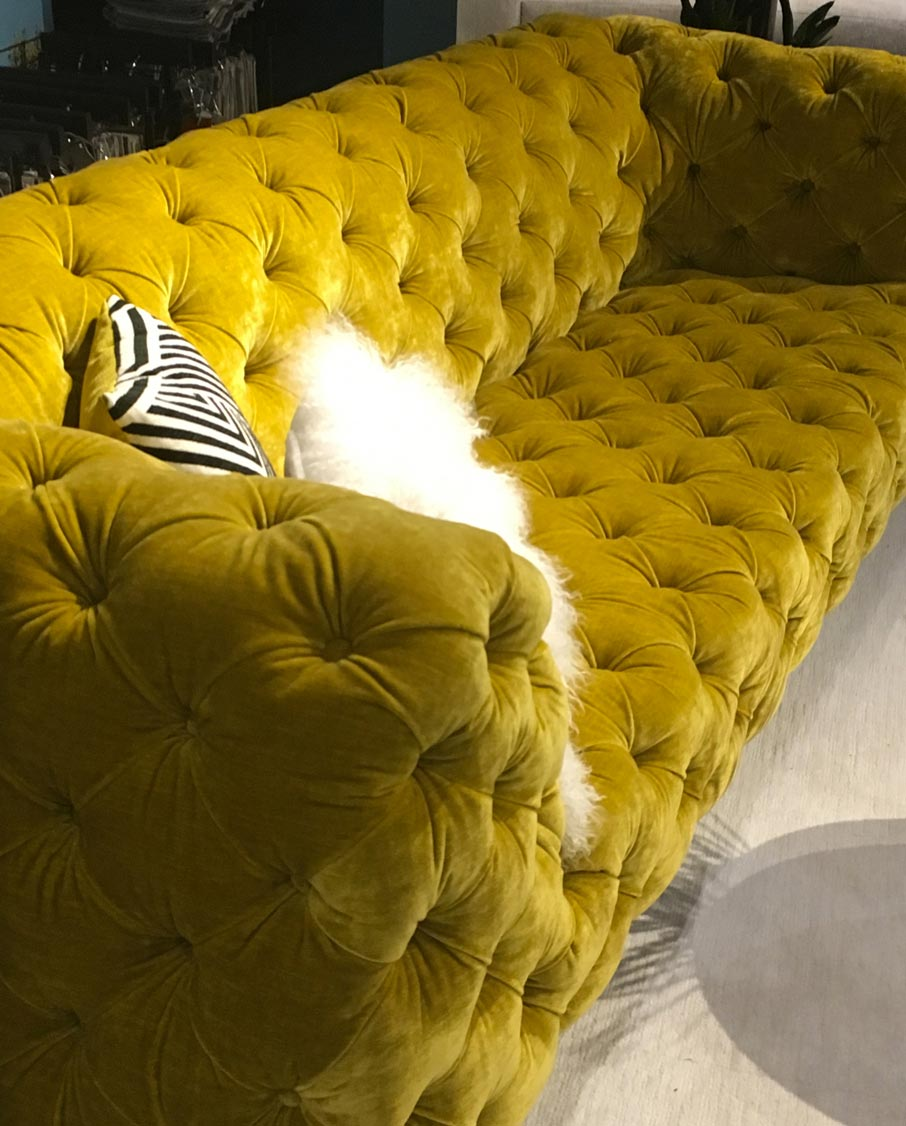 Pouffy-yellow-velvet-couch-on-display-with-exotic-cushions