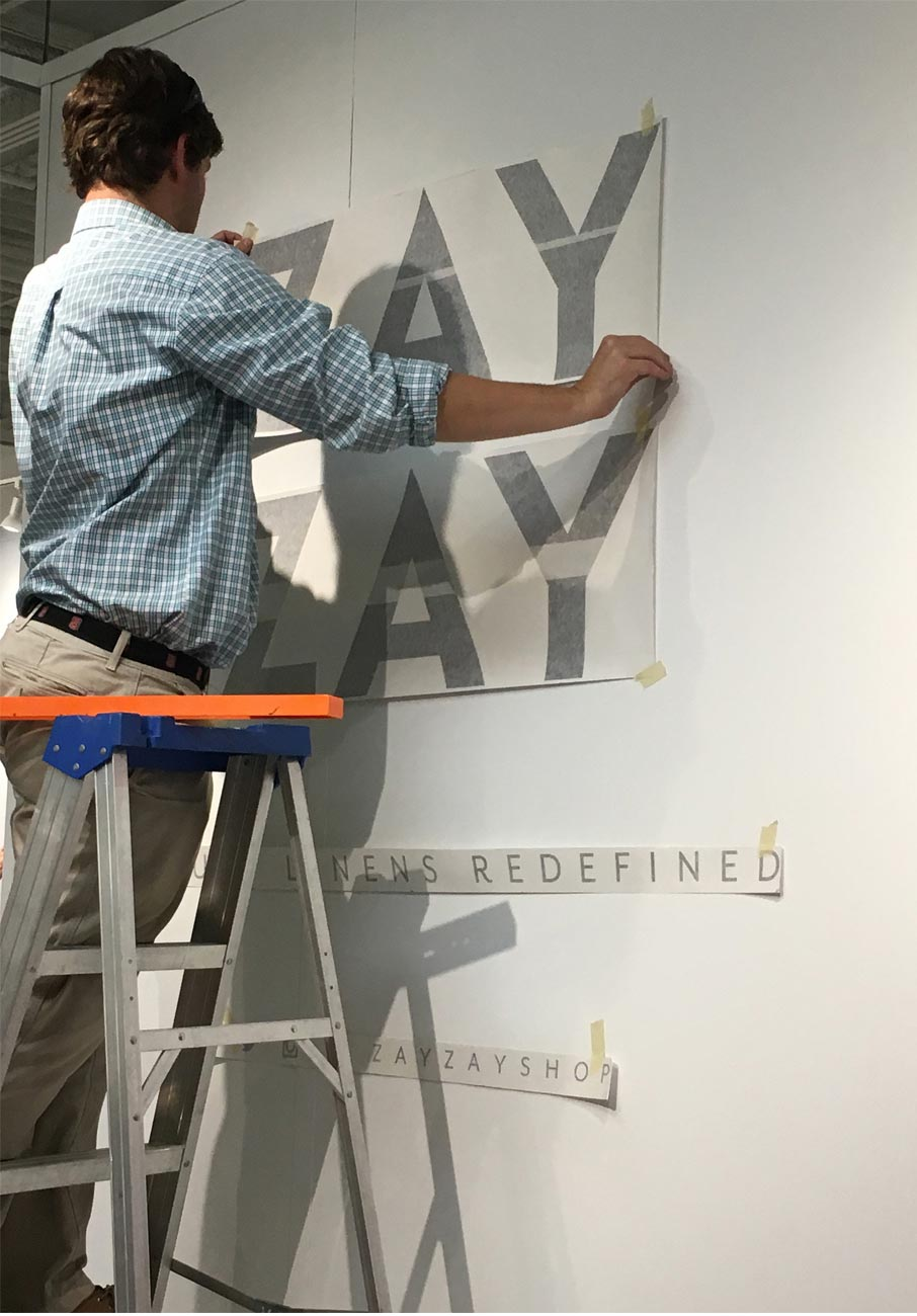 Sir-Speedy-Printing-installing-wall-signage-for-ZayZay-exhibit-at-Market-Square