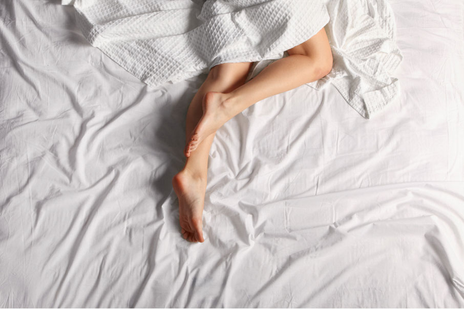 Woman-sleeping-under-white-sheet-legs-exposed-to-cool-off