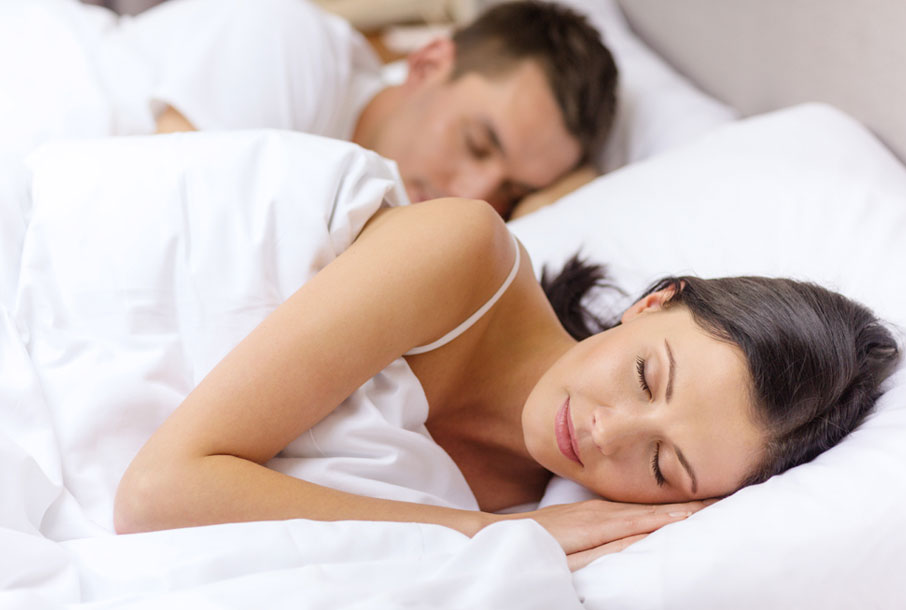 Young-couple-sleeping-beside-each-other-in-bed-under-white-sheets