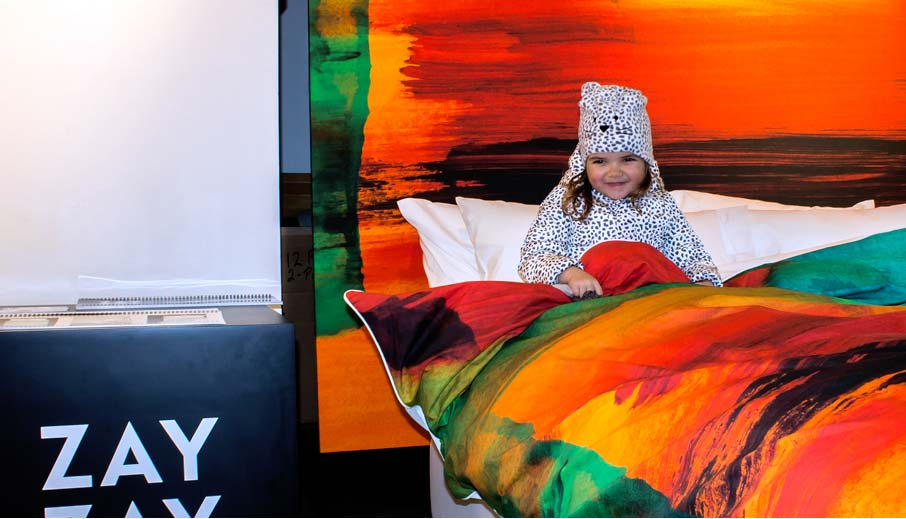 Young-girl-snuggling-into-ZayZay-popup-display-bed-with-African-Sunset-design