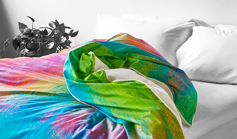 ZayZay-pink-green-blue-Tropical-Frost-duvet-cover-tossed-open-on-bed-in-black-and-white-room