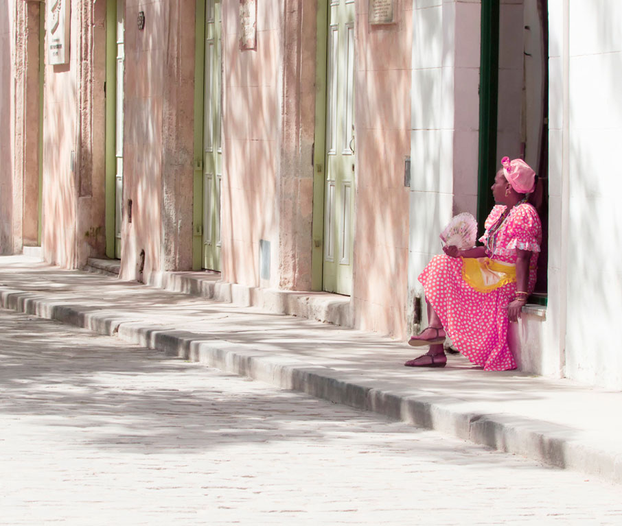 Cuban-woman-in-pink-polka-dot-dress-sitting-on-windowsill-of-architectural-entrance