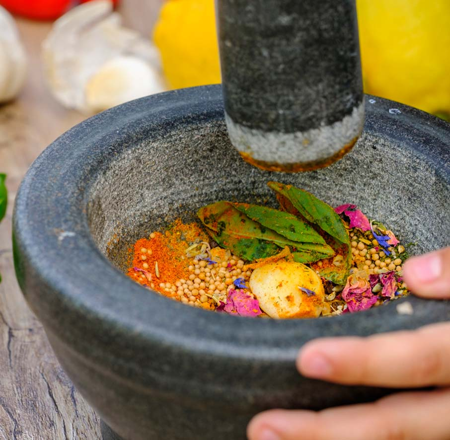 Gray-mortar-and-pestle-with-colourful-herbs-and-spices