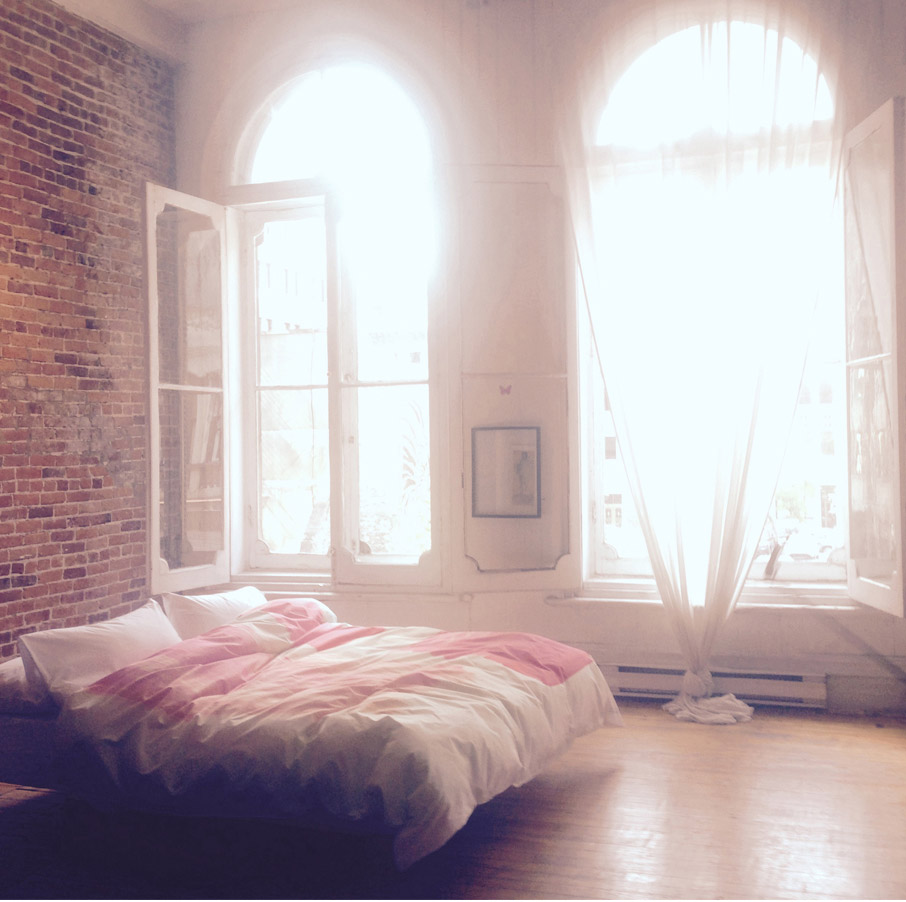 Soft-lit-bedroom-brick-wall-tall-windows-lots-of-light-with-ZayZay-So-Jess--duvet-cover-on-bed