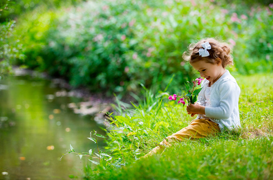 Young-girl-sitting-on-grass-holding-flowers-by-river-bank