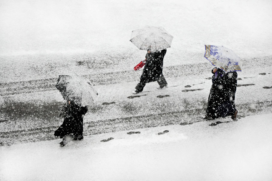 People-walking-under-umbrellas-for-shelter-from-snow-freezing-rain
