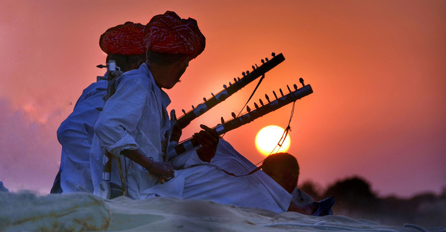 Two Indian men playing instruments against orange pink sunset in the distance