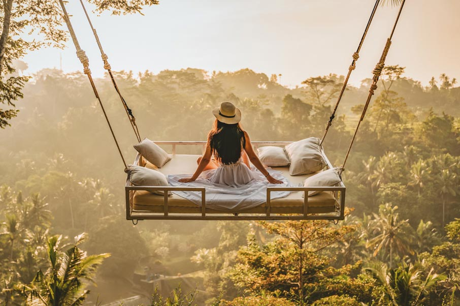 Woman on bed swing above tropical forest